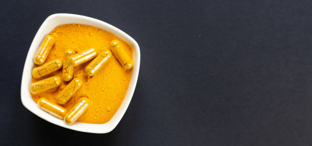 Top view of turmeric powder and capsules in a small white bowl on dark background, which looks like DNP
