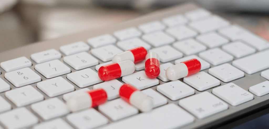 Red and white capsules on a computer keyboard