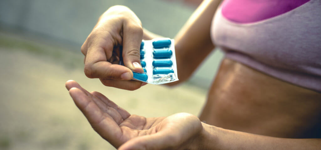 Close up of unrecognizable female athlete taking pills before sports training.