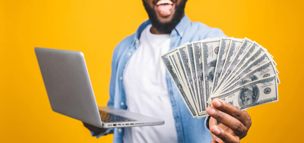 Photo of a happy young afro american handsome man posing isolated over yellow wall background using laptop computer holding money.